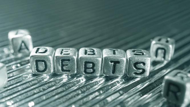 """Würfel mit der Aufschrift """"DEBTS"""""""